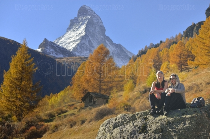Two girls and autumn scene in zermatt with matterhorn mountain
