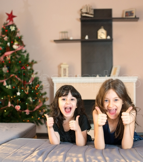 Two little sisters doing ok sign that Christmas is coming