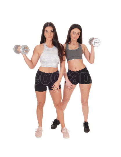 Two woman exercising with dumbbells in the studio