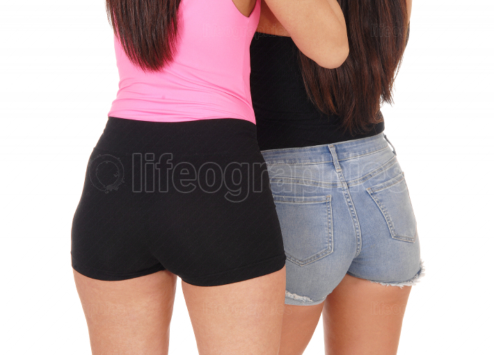 Two women standing from the back in jeans shorts
