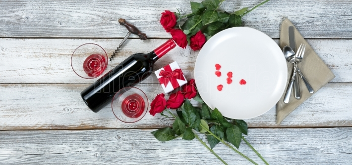 Valentine dinner with wine and roses on rustic wooden table