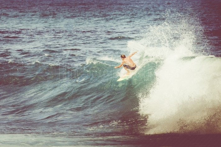 Vintage photo professional surfer rides a giant wave.