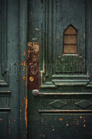 Vintage weathered green wooden door with metal doorknob