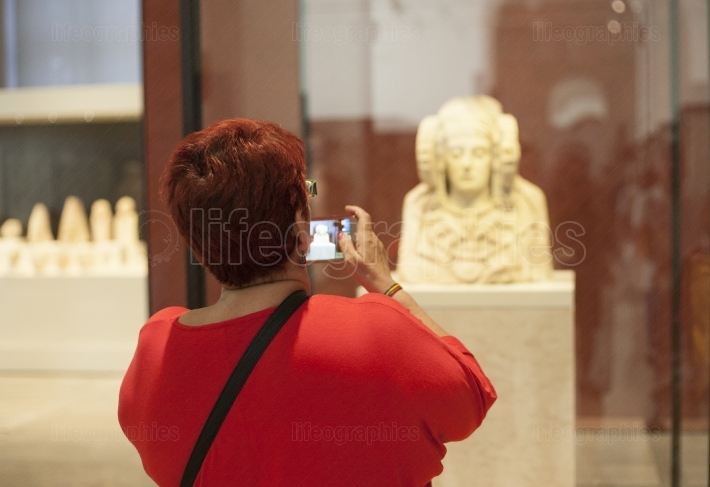 Visitor taking pictures Lady of Elche