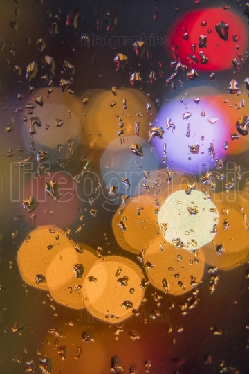 Water drops on window with color background