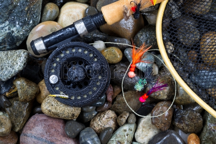 Wet Trout fishing gear on river rocks