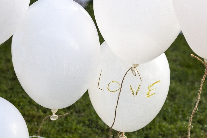 White balloons over grass saying  Love  at a wedding reception