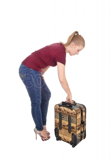 Woman bending down for her suitcase