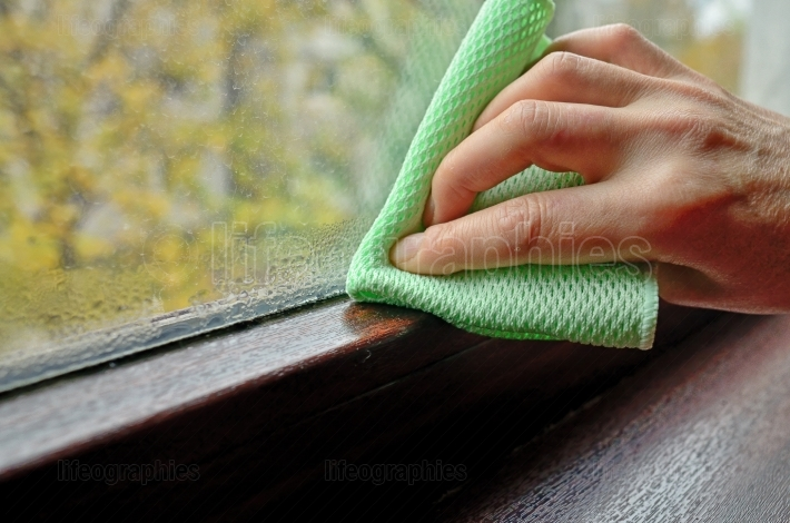 Woman cleaning water  condensation on window