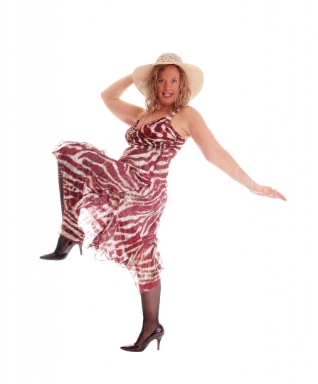 Woman dancing in dress and hat.