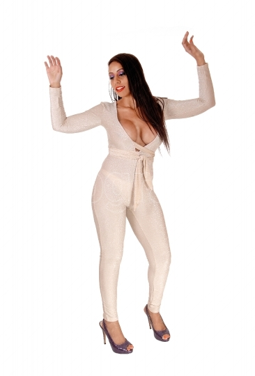 Woman dancing in silver jumpsuit with eyes closed