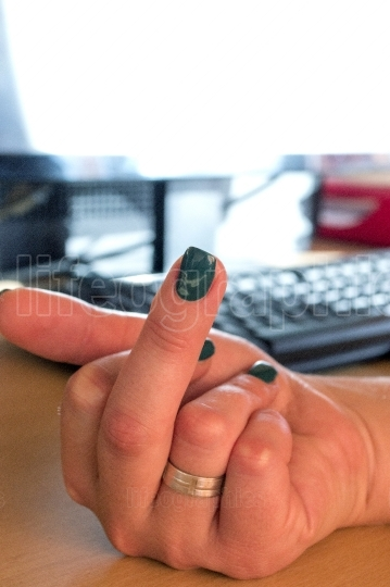 Woman fingers with green nail polish and bad gesture