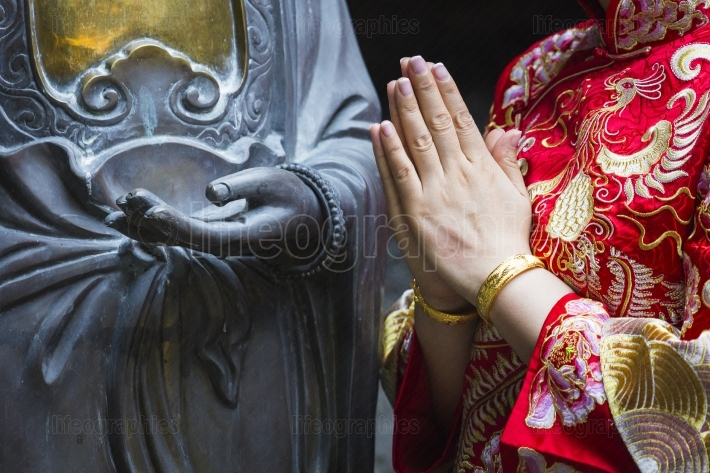 Woman hand respect to buddha statue.