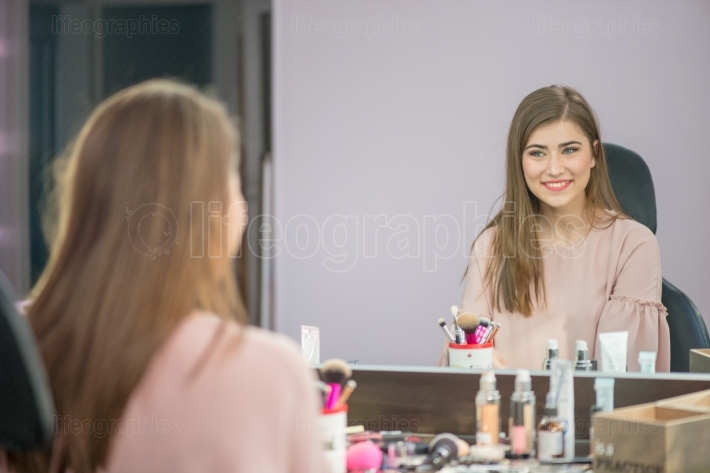 Woman in a beauty salon looks at her reflection in the mirror with lamps and checks hairstyle and makeup
