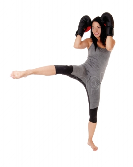 Woman in kick boxing action fighting