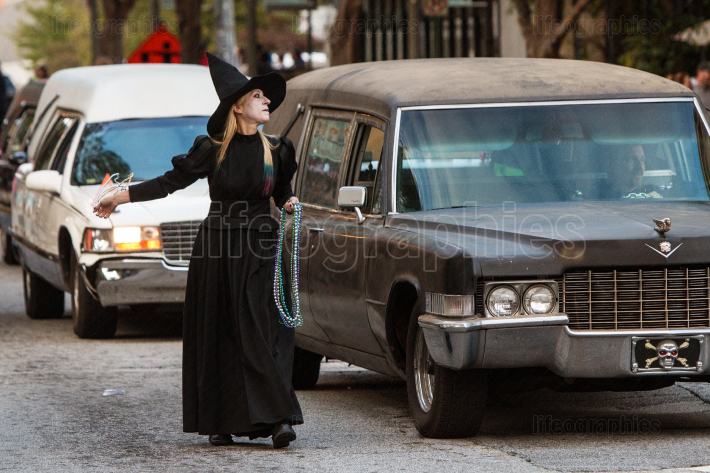Woman In Witch Costume Walks Alongside Hearses At Halloween Parade