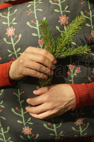 Woman is holding pine branch and pillow