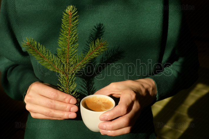 Woman is holding pine tree branch and an espresso