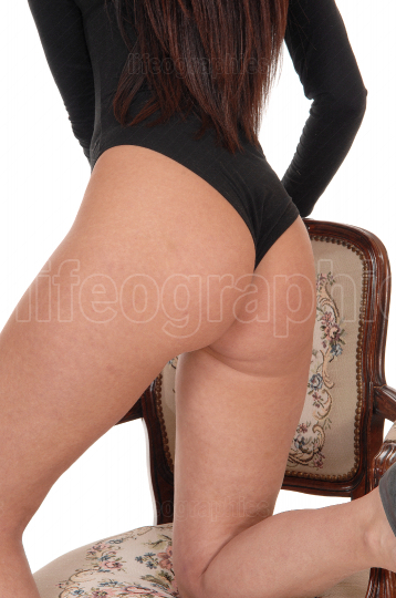 Woman kneeling from back in black body suit in a chair
