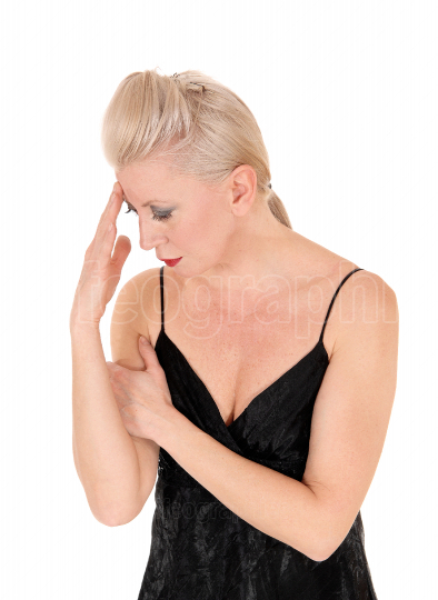Woman looking down hand on head thinking