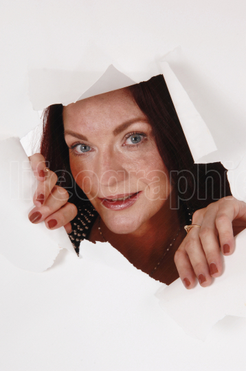 Woman looking through a hole in the paper