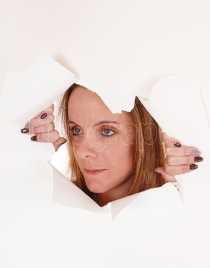 Woman looking trough a hole in a white paper