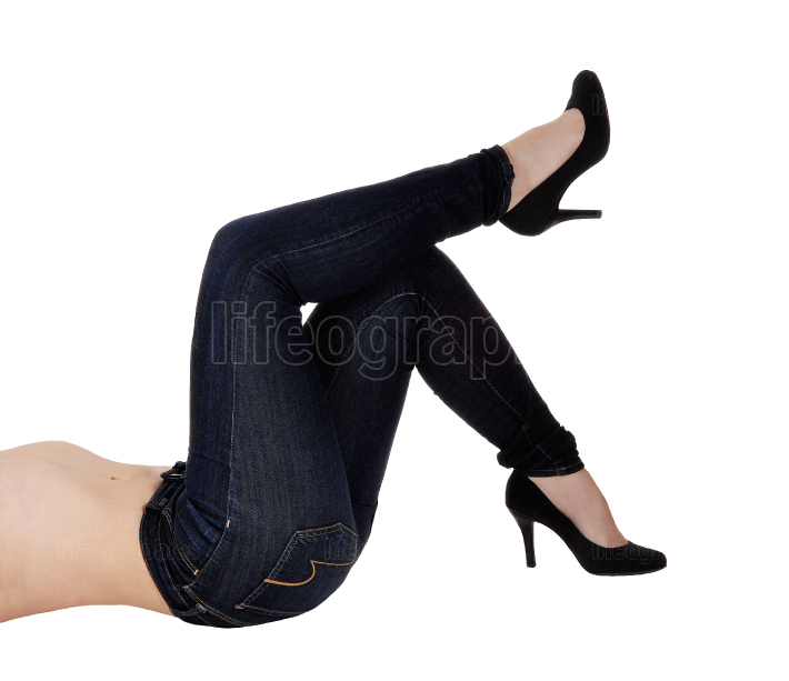 Woman lying in jeans and high heels on the floor