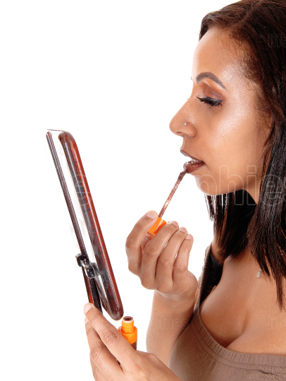 Woman putting color on her lips holding mirror