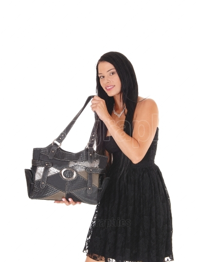 Woman showing of her new purse in a black dress