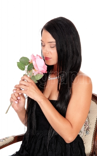 Woman sitting in armchair smiling pink roses