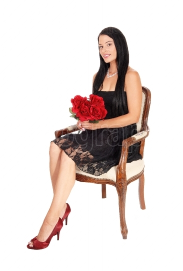 Woman sitting in armchair with red roses