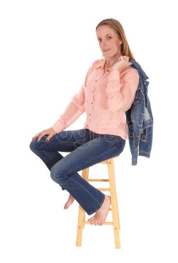 Woman sitting on chair, jacket over shoulder