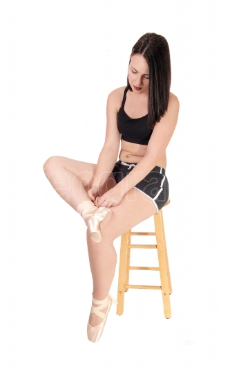 Woman sitting on chair tying up her ballet shoe