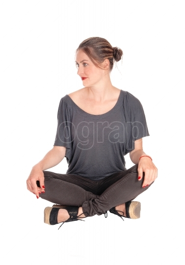 Woman sitting with closed legs on floor