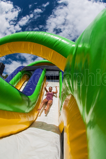 Woman Slides Down Obstacle Course Inflatable Slide At Fitness Event