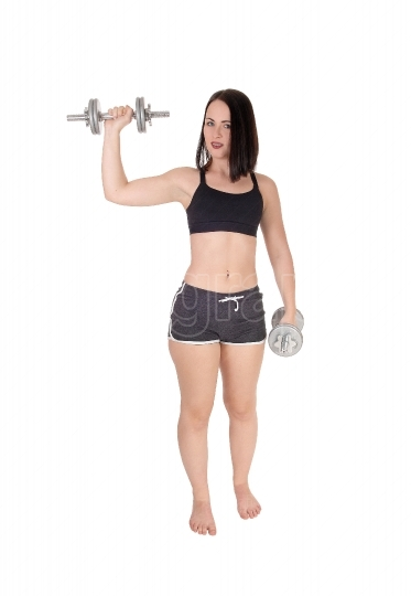 Woman standing bare feet and lifting two dumbbells