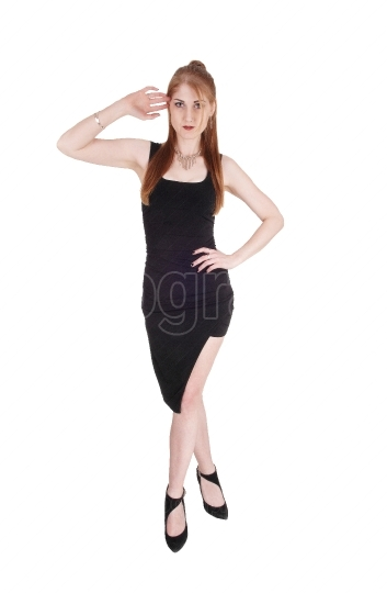 Woman standing in a black dress and heels