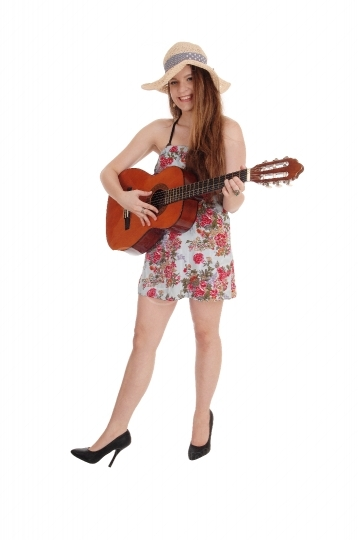 Woman standing in a dress with her guitar