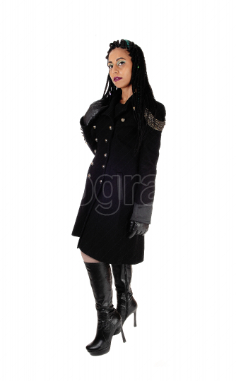 Woman standing in a long black coat and boots
