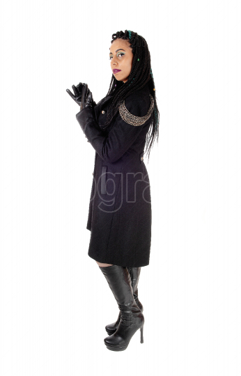 Woman standing in black coat and boots