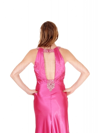 Woman standing in pink dress from the back