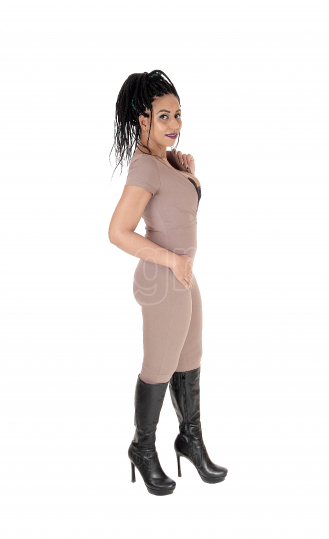 Woman standing in profile in beige jumpsuit and boots
