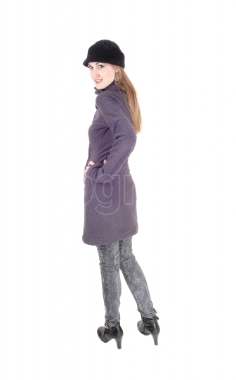 Woman standing in winter coat looking over shoulder