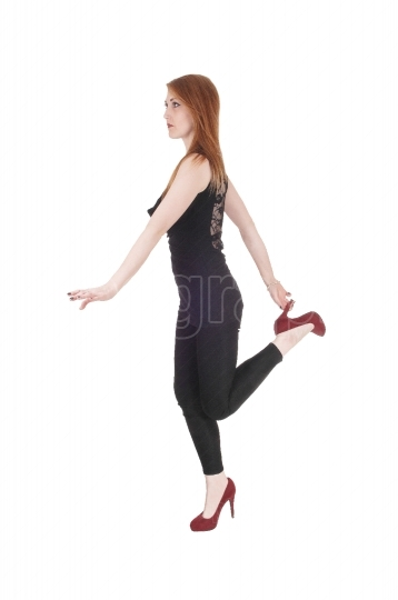 Woman standing on one leg holding heels