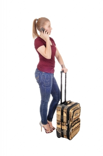 Woman standing with suitcase talking on phone