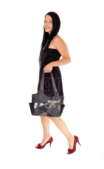 Woman walking in black dress and purse