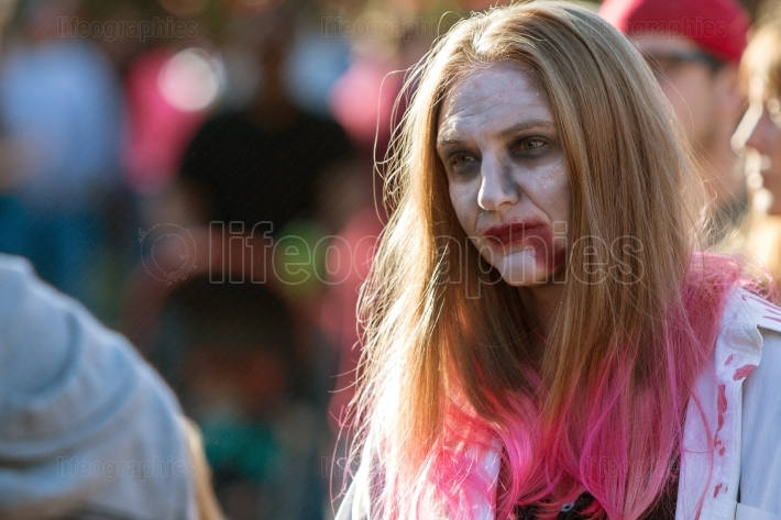 Woman Wearing Zombie Makeup Wanders Through Crowd At Halloween F