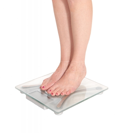 Womans legs standing on a glass scale