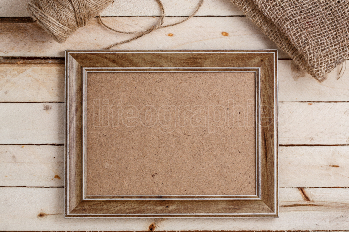 Wooden photo frames on light wooden background with canvas