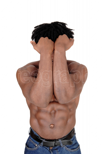 Young African man standing shirtless with his arms over his face